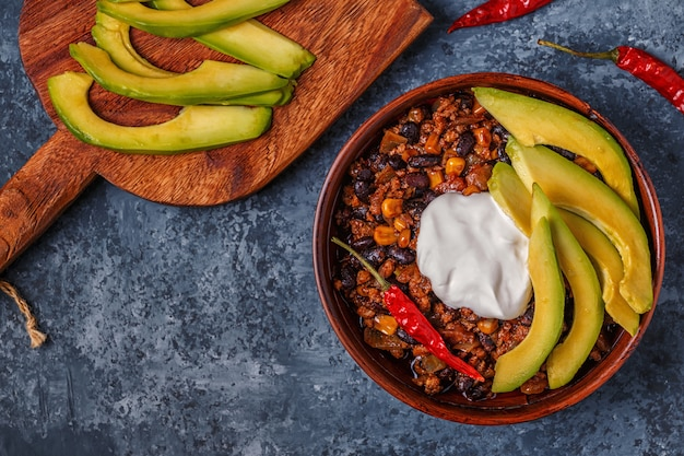Chili con carne w misce z awokado i kwaśną śmietaną.