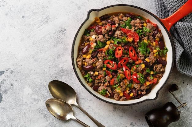 Chili con carne z mięsem mielonym i gulaszem warzywnym w sosie pomidorowym na żeliwnej patelni na jasnoszarym łupku lub betonowej powierzchni