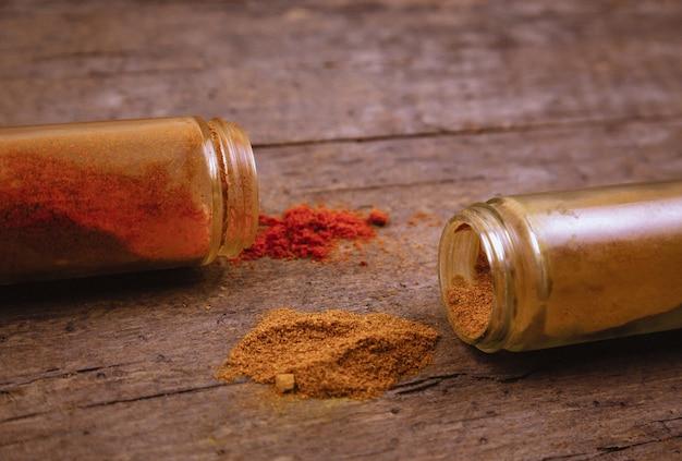 Chili kolorowe prochowe pikantność rozpraszać od butelki na drewnianym tle