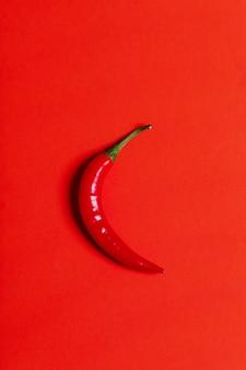 Chili pieprz odizolowywający na czerwieni, odgórny widok