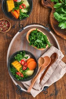 Chilijska zupa mięsna z pampkinem, kukurydzą, świeżą kolendrą i ziemniakami na starym drewnianym stole tle. cazuela. kuchnia latynoamerykańska.