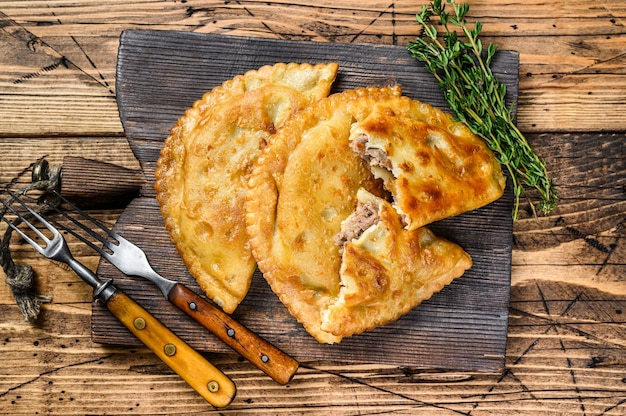 Chilijskie smażone empanady nadziewane mielonym mięsem wołowym podawane na drewnianej desce do krojenia