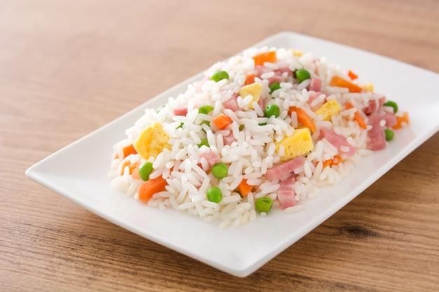 Chińczycy smażący ryż z warzywami i omletem na drewnianym stole
