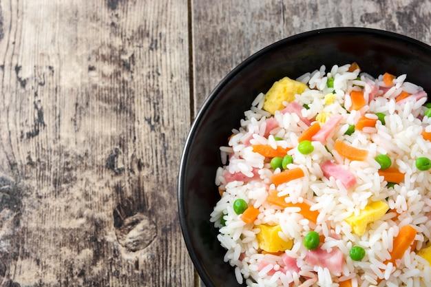 Chińczyk smażący ryż z warzywami i omletem w czarnym pucharze na drewnianym stole