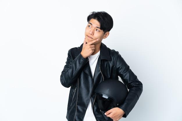 Chińczyk w kasku motocyklowym na białym tle ma wątpliwości