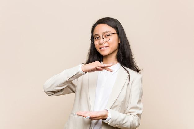 Chinka młody biznes coś obiema rękami, prezentacja produktu.
