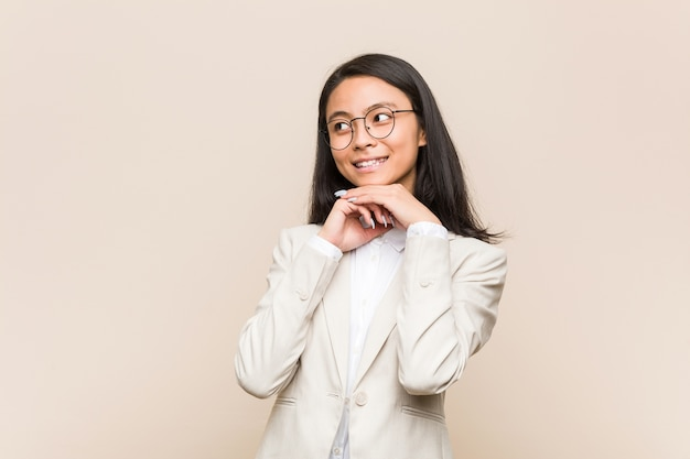 Chinka młody biznes trzyma ręce pod brodą, patrzy szczęśliwie na bok.