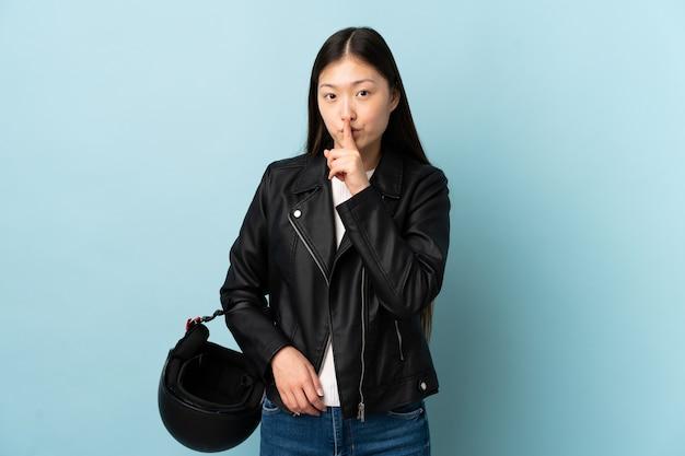 Chinka trzyma kask motocyklowy na niebiesko, robi gest ciszy