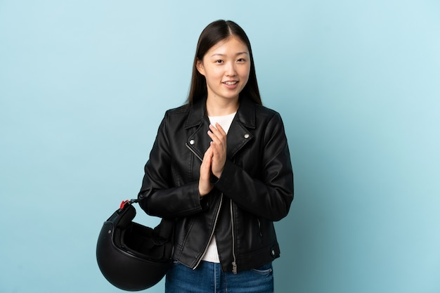 Chinka trzyma kask motocyklowy na pojedyncze niebieskie ściany oklaskiwać