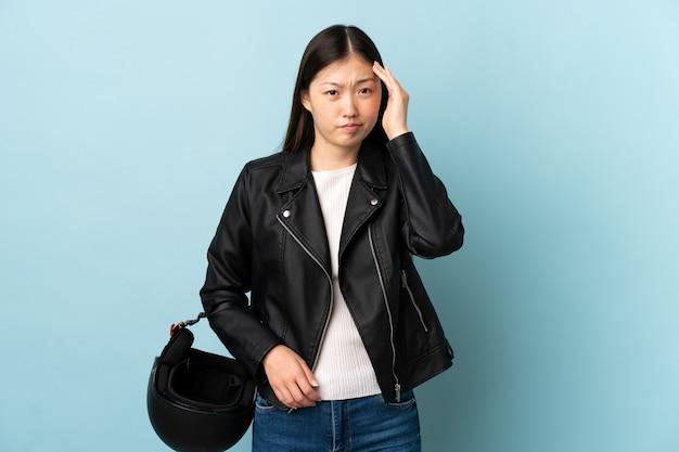 Chinka trzyma kask motocyklowy nad odizolowaną niebieską ścianą niezadowolony i sfrustrowany czymś. negatywny wyraz twarzy