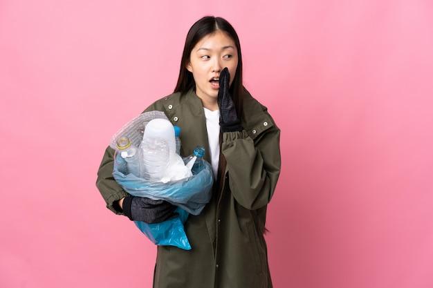 Chinka trzyma torbę pełną plastikowych butelek, aby poddać recyklingowi nad izolowaną różową ścianą szepcząc coś z zaskoczenia gestem, patrząc w bok
