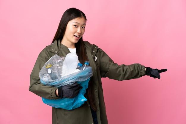 Chinka trzyma torbę pełną plastikowych butelek do recyklingu na białym tle