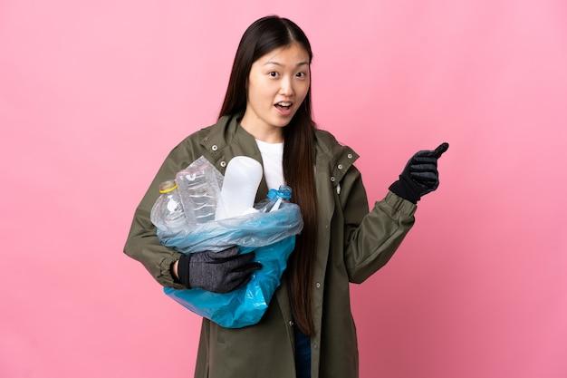 Chinka trzyma torbę pełną plastikowych butelek do recyklingu na izolowanym różowym tle, zaskoczona i wskazując palcem w bok