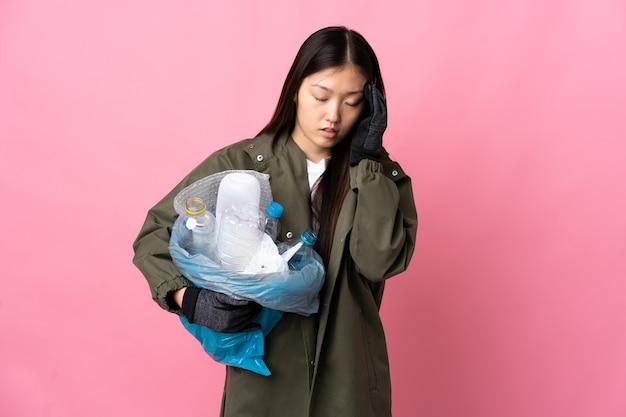 Chinka trzyma torbę pełną plastikowych butelek do recyklingu na pojedyncze różowe tło z bólem głowy