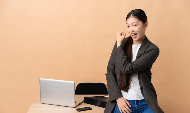 Chińska biznesowa kobieta świętuje zwycięstwo w jej miejscu pracy