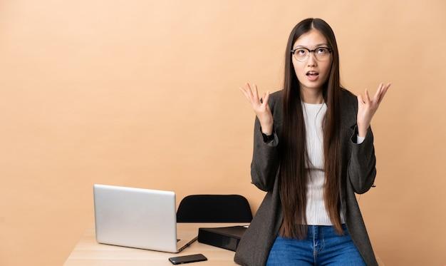 Chińska biznesowa kobieta w jej miejscu pracy stresował się przytłaczającym