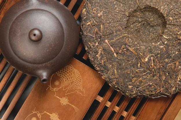 Chińska ceremonia parzenia herbaty. czajnik ceramiczny wykonany z gliny i miski na drewnianym tle.