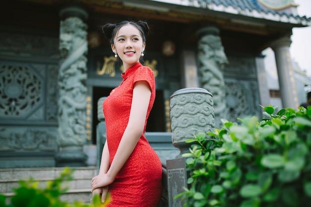 Chińska dziewczyna ono uśmiecha się przy porcelanową świątynią w tradycyjnej sukni
