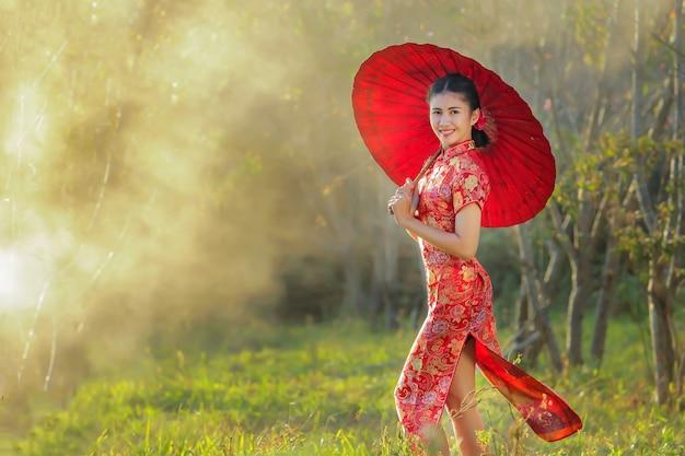 Chińska dziewczyna z smokingowym tradycyjnym cheongsam w ogródzie