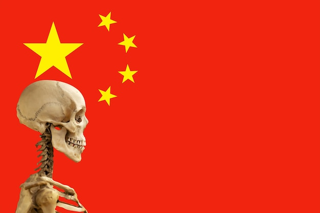 Chińska flaga ze szkieletem. pojęcie śmierci z powodu zakażenia wirusem wieńcowym.