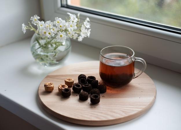 Chińska herbata puer w filiżance na oknie, tradycyjny chiński puerh tłoczony