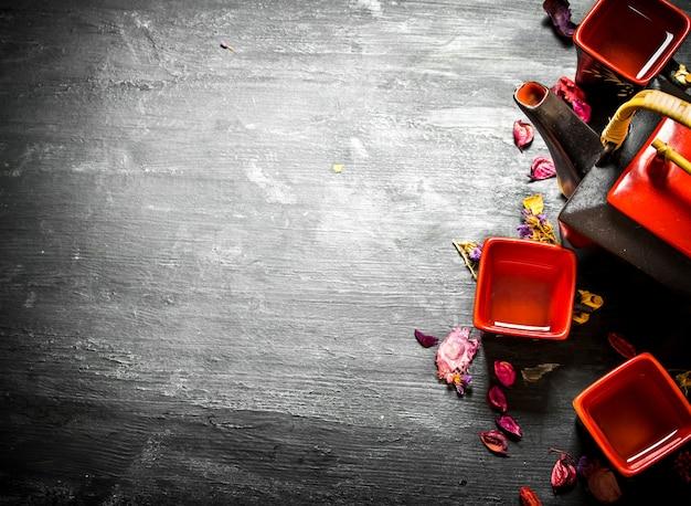 Chińska herbata z kwiatami i ziołami na czarnym tle drewnianych
