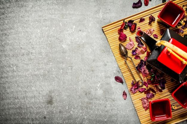 Chińska herbata z ziołami i suszonymi owocami na kamiennym stole.