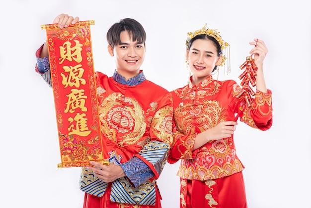 Chińska kartka okolicznościowa i petarda są używane przez mężczyznę i kobietę noszących garnitur cheongsam, aby świętować chiński nowy rok