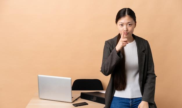 Chińska kobieta biznesu w swoim miejscu pracy sfrustrowana i wskazując na przód
