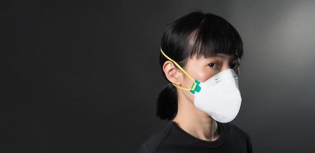 Chińska kobieta w średnim wieku nosząca medyczną maskę n95, która pomaga zapobiegać lub chronić ją przed