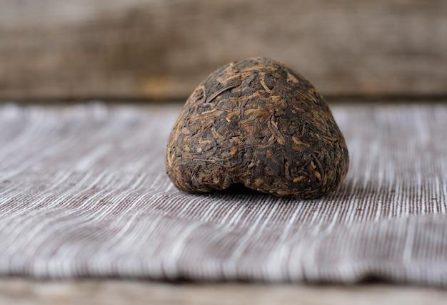 Chińska stara herbata shen puer w formie gniazda na stole