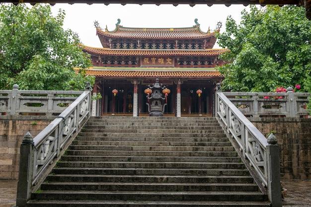"""Chińska tradycyjna architektura buddyjska w deszczu, tablica z napisem """"sala mahaviry"""""""