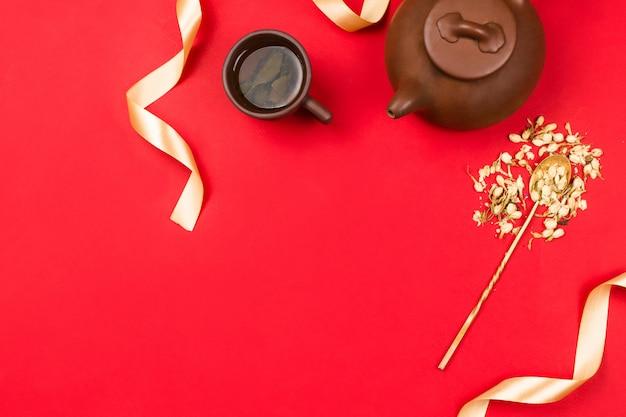 Chińska zielona herbata, kwiaty jaśminu w złotej łyżce i złote wstążki