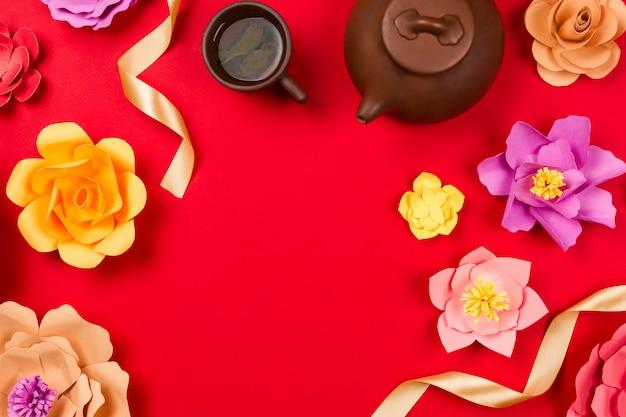 Chińska zielona herbata w filiżance, gliniany czajniczek i piękne papierowe kwiaty