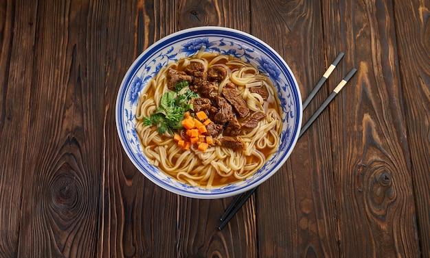 Chińska zupa z makaronem wołowym w tradycyjnej niebieskiej misce, świeże zioła i pokrojona marchewka, para pałeczek na ciemnym drewnianym stole i miejsce na kopię. widok z góry koncepcja kuchni azjatyckiej