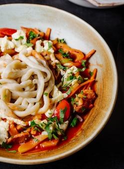 Chińska zupa z makaronem z warzywami w sosie pomidorowym