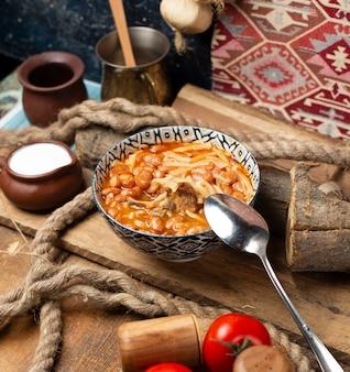 Chińska zupa z makaronem z ziołami i przyprawami w ozdobnej misce.