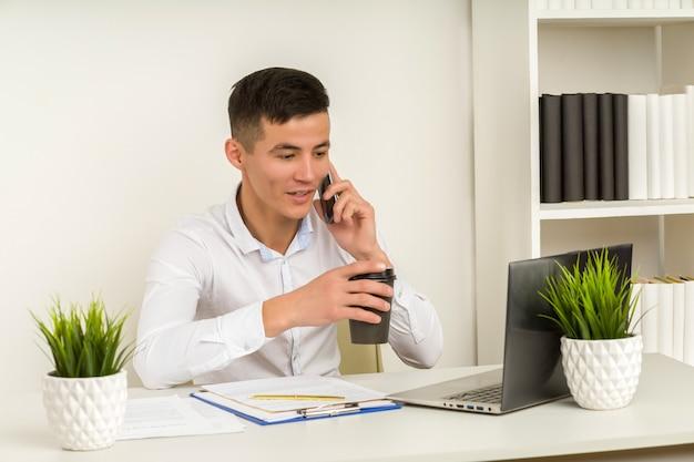 Chiński azjatycki biznes mężczyzna rozmawia przez telefon komórkowy i pracuje na swoim laptopie w biurze
