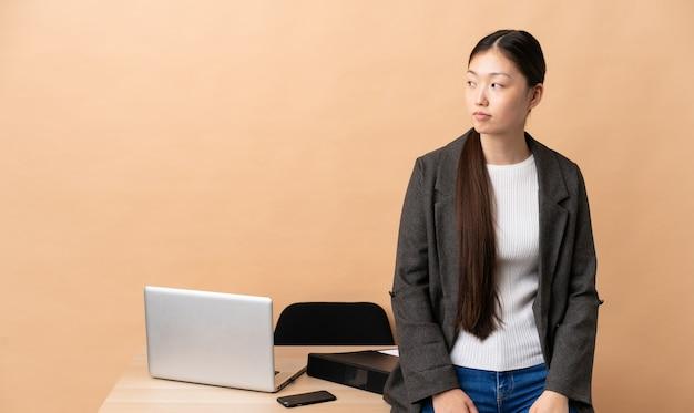Chiński biznes kobieta w swoim miejscu pracy, patrząc z boku