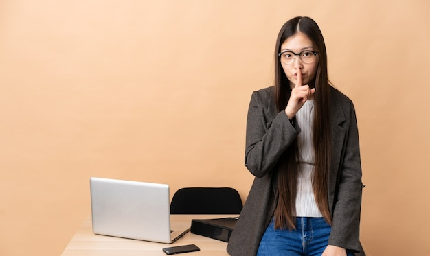 Chiński biznes kobieta w swoim miejscu pracy pokazując znak gestu ciszy wkładając palec w usta