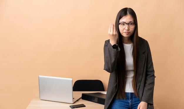 Chiński biznesowa kobieta w swoim miejscu pracy czyniąc włoski gest