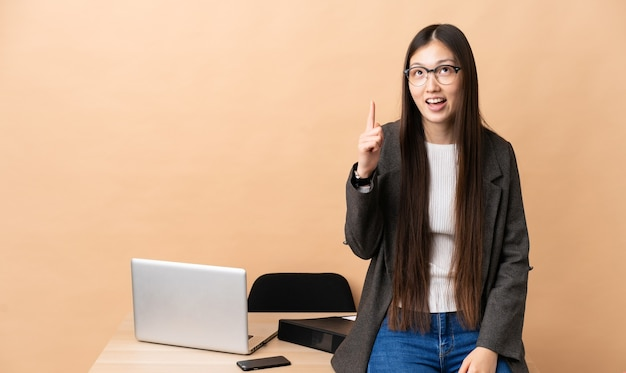 Chiński biznesowa kobieta w swoim miejscu pracy wskazuje w górę i zaskoczony