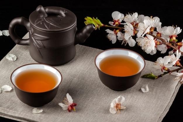 Chiński brązowy czajnik i filiżanki na czarnym drewnianym stole