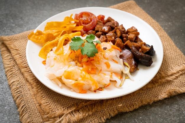 Chiński makaron ryżowy gotowany na parze z wieprzowiną i tofu w słodkim sosie sojowym