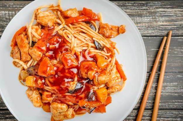 Chiński makaron w sosie słodko-kwaśnym i pałeczkami na stole