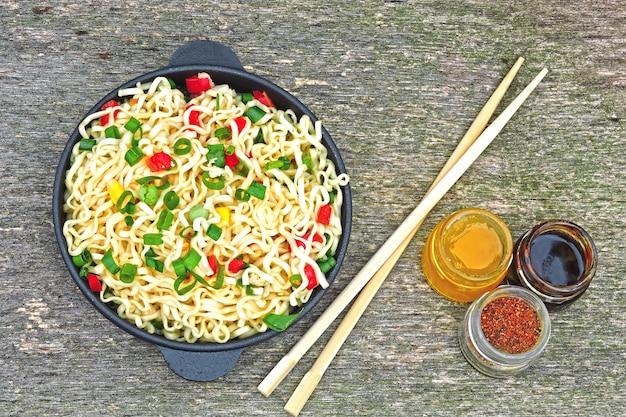 Chiński makaron w żeliwnej misce. gorący chiński makaron.