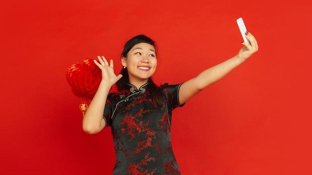 Chiński nowy rok 2020. portret młodej dziewczyny azji na białym tle na czerwonym tle. modelka w tradycyjnych strojach wygląda na szczęśliwą i robi selfie z dekoracją. uroczystość, święto, emocje. ulotka.