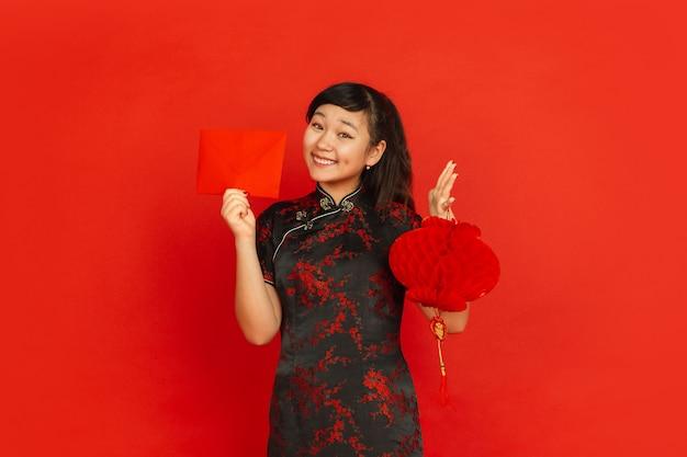 Chiński nowy rok 2020. portret młodej dziewczyny azji na białym tle na czerwonym tle. modelka w tradycyjnych strojach wygląda na zadowoloną z dekoracją i czerwoną kopertą. uroczystość, święto, emocje.