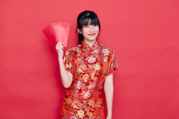 Chiński nowy rok młoda kobieta ma na sobie czerwony cheongsam holding envelope