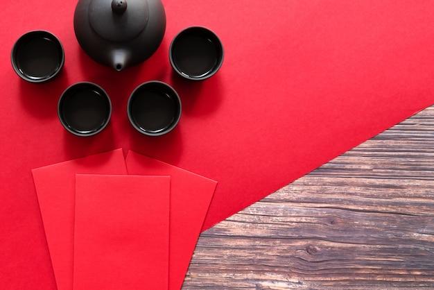 Chiński nowy rok oferuje czerwoną kopertę i chiński dzbanek do herbaty